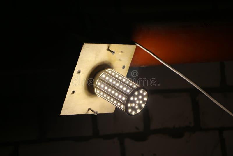 LED lamp mounted on wooden board to illuminate dark room. LED lamp mounted on a wooden board to illuminate a dark room royalty free stock photo