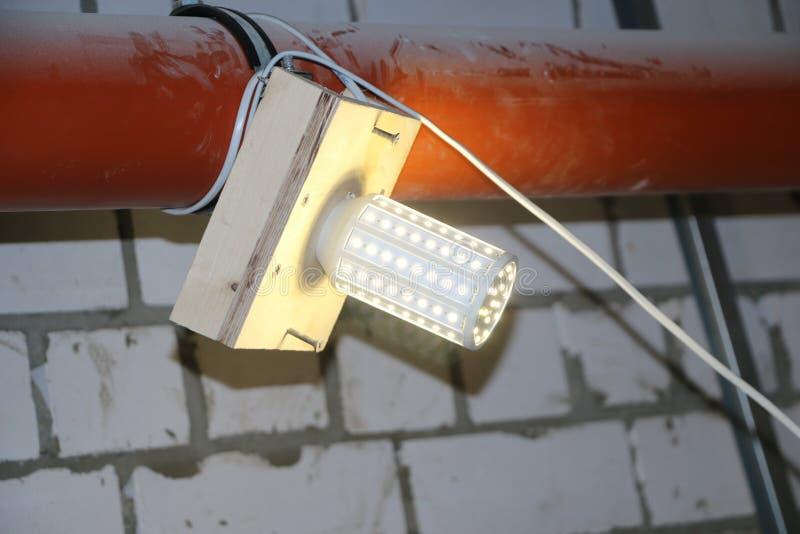 LED lamp mounted on wooden board to illuminate dark room. LED lamp mounted on a wooden board to illuminate a dark room stock photo