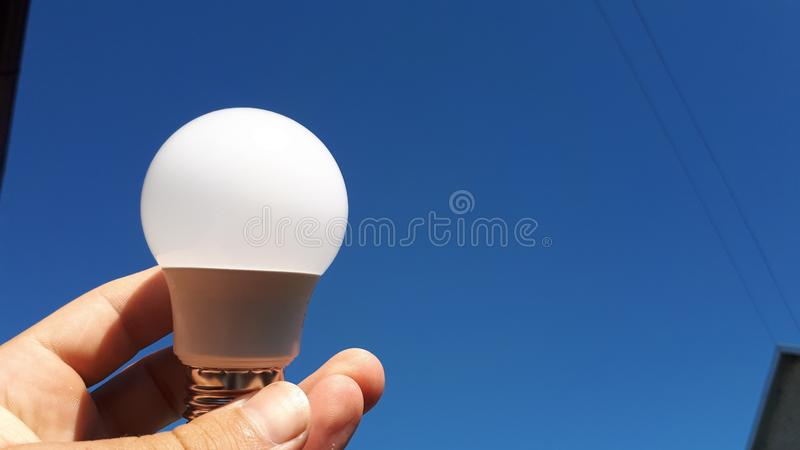 LED light bulb on blue sky background in human hand. Electricity concept. royalty free stock image
