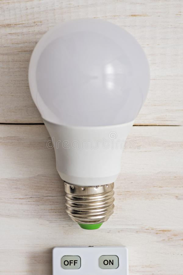 LED light bulb and remote control with buttons on and off on a white wooden background.  royalty free stock images