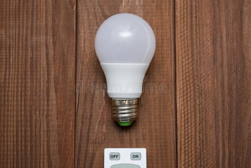 LED light bulb and remote control with buttons on and off on a wooden background stock photography