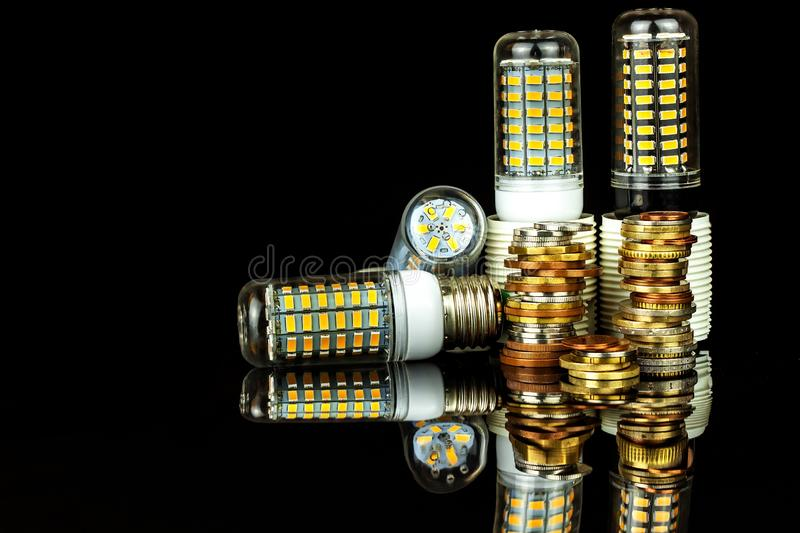 Led light bulbs and coins on a black background. Saving power. Ecological lighting. Saving money.  royalty free stock photos