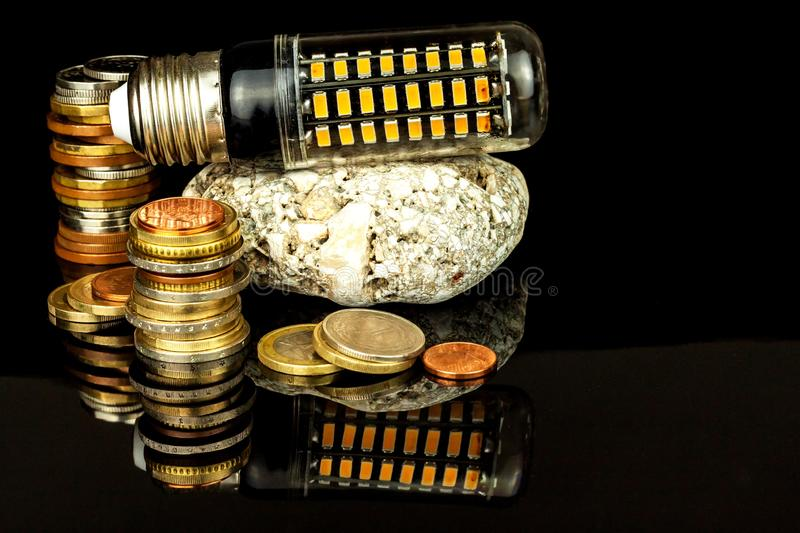 Led light bulbs and coins on a black background. Saving power. Ecological lighting. Saving money.  stock images