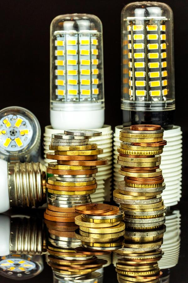 Led light bulbs and coins on a black background. Saving power. Ecological lighting. Saving money.  royalty free stock image