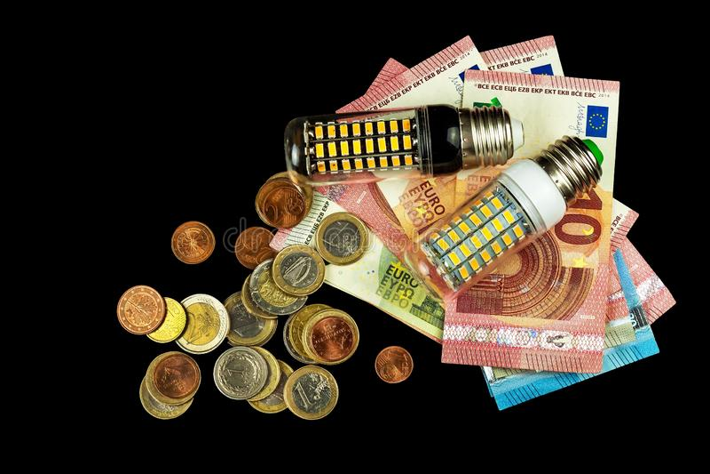 Led light bulbs and coins on a black background. Saving power. Ecological lighting. Saving money.  stock photos