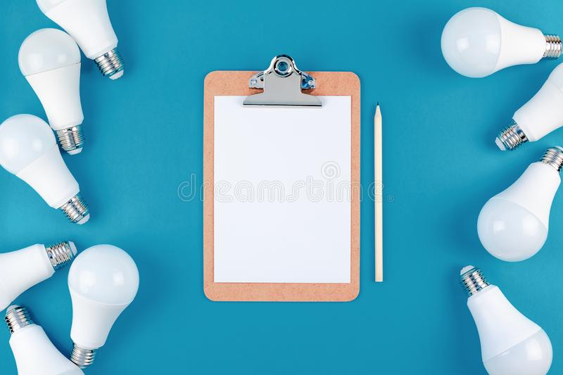 LED light bulbs frame and blank paper in clipboard. Energy-saving and eco-friendly life in conceptual composition. Creative top view flat lay of LED light bulbs royalty free stock photography