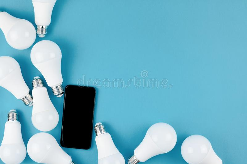 LED light bulbs and modern smartphone mockup. Energy-saving and eco-friendly life in conceptual frame pattern. Creative top view flat lay of LED light bulbs and stock image