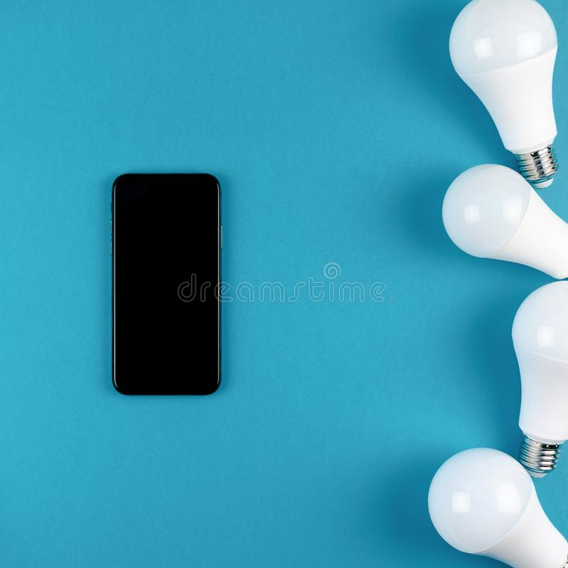 LED light bulbs and modern smartphone mockup. Energy-saving and eco-friendly life in conceptual frame pattern. Creative top view flat lay of LED light bulbs and stock images