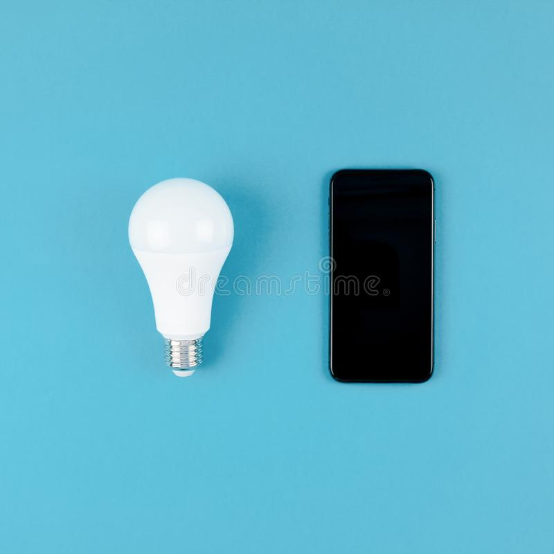 LED light bulbs and modern smartphone mockup. Energy-saving and eco-friendly life in conceptual frame pattern. Creative top view flat lay of LED light bulbs and stock photos