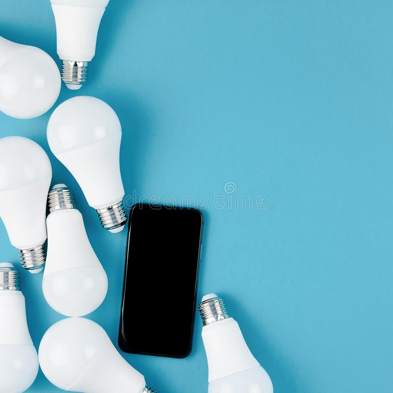 LED light bulbs and modern smartphone mockup. Energy-saving and eco-friendly life in conceptual frame pattern. Creative top view flat lay of LED light bulbs and stock photography