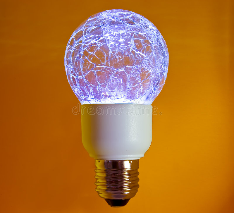 LED Lightbulb. A lit light bulb on orange background stock photos