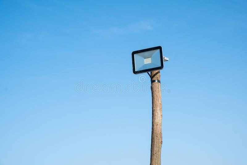 Led street lamp mounted on a wooden tree trunk. Against a blue sky stock images