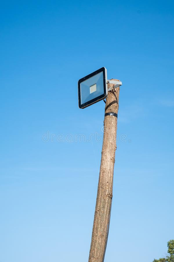 Led street lamp mounted on a wooden tree trunk. Against a blue sky royalty free stock image