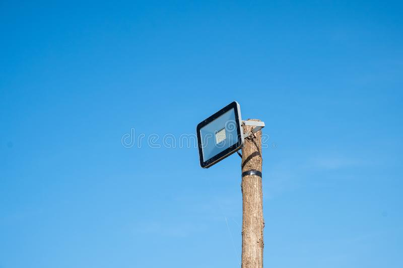 Led street lamp mounted on a wooden tree trunk. Against a blue sky stock photos