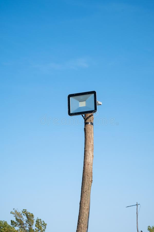 Led street lamp mounted on a wooden tree trunk. Against a blue sky stock image