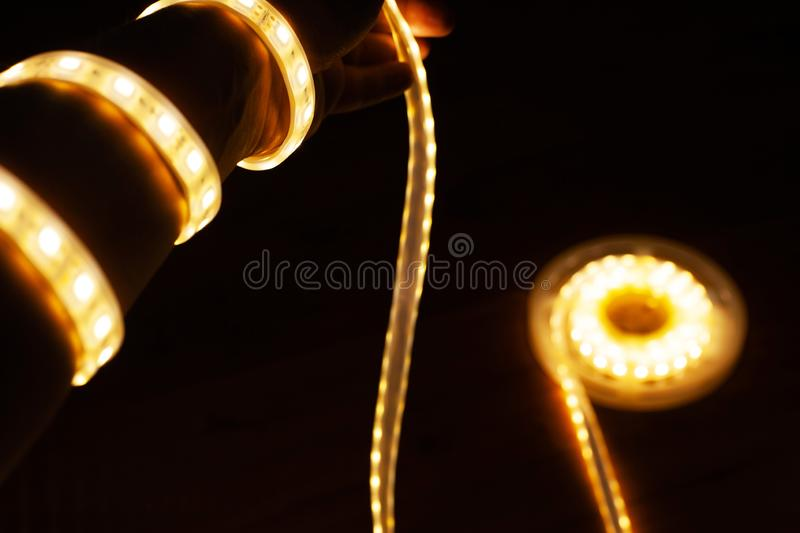 LED tape on hand, diode tape wound like a garland. Close up stock image