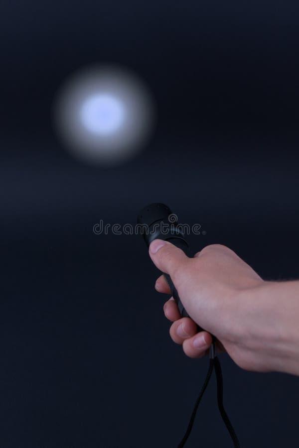 LED-Taschenlampe mit einem Lichtstrahl in der Hand stockbild