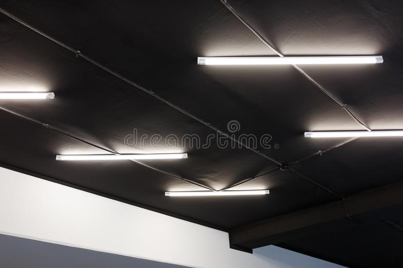 Led tube lights on black office ceiling. Minimal loft design.  royalty free stock photos