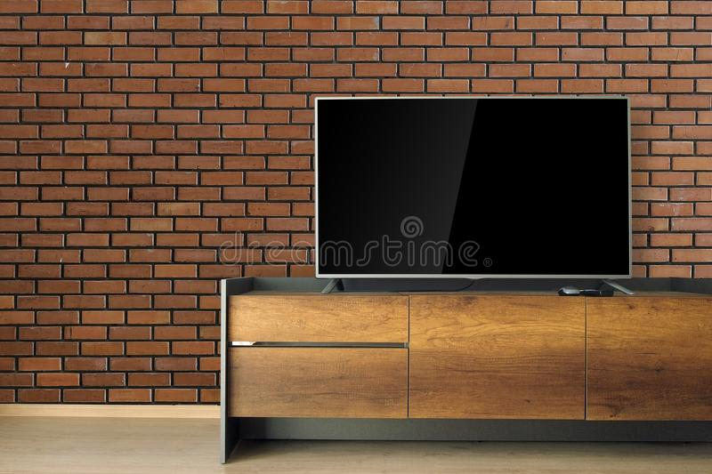 Led TV on TV stand in empty room with red brick wall. decorate i stock photography