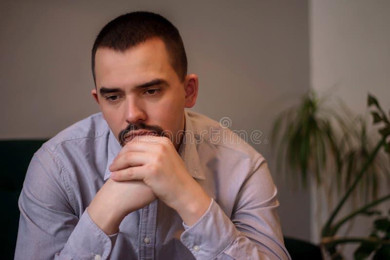 Leda, f?rdjupning och mentalt hedfr?gebegrepp: olycklig vuxen man i den rynkiga skjortan som sitter i rum som har satt hakan p? h royaltyfri bild