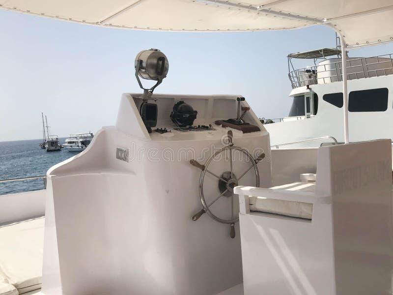 Leda kabinen för ` s på ett skepp, fartyget, kryssningeyeliner med ett styrninghjul och instrument för kontroll mot det blåa have arkivbild