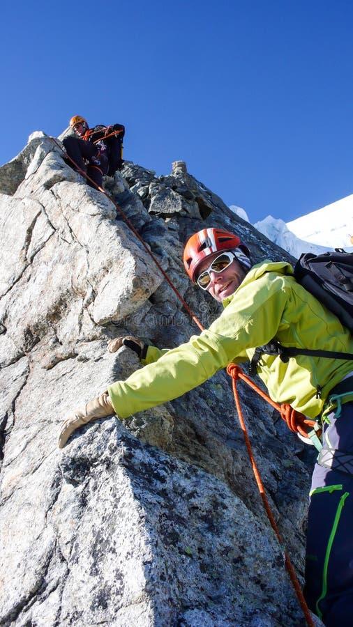 Ledande manlig klient för berghandbok till toppmötet av ett högt alpint maximum på en härlig sommardag fotografering för bildbyråer