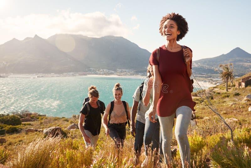 Ledande vänner för Millennial afrikansk amerikankvinna på en stigande vandring vid kusten, slut upp royaltyfri foto