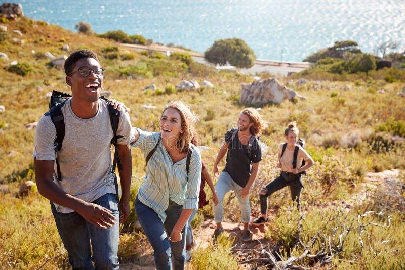 Ledande vänner för Millennial afrikansk amerikanman som fotvandrar gåsmarschen som är stigande på en bana vid kusten royaltyfri foto