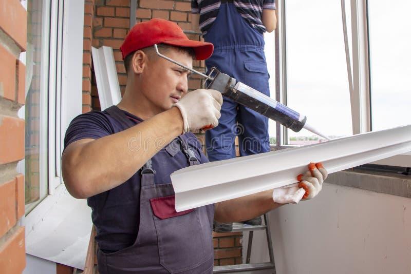 Ledar- arbetare installerar fönsterfönsterbrädareparation i asiat för husbyggnad som limmas med silikonet arkivbild