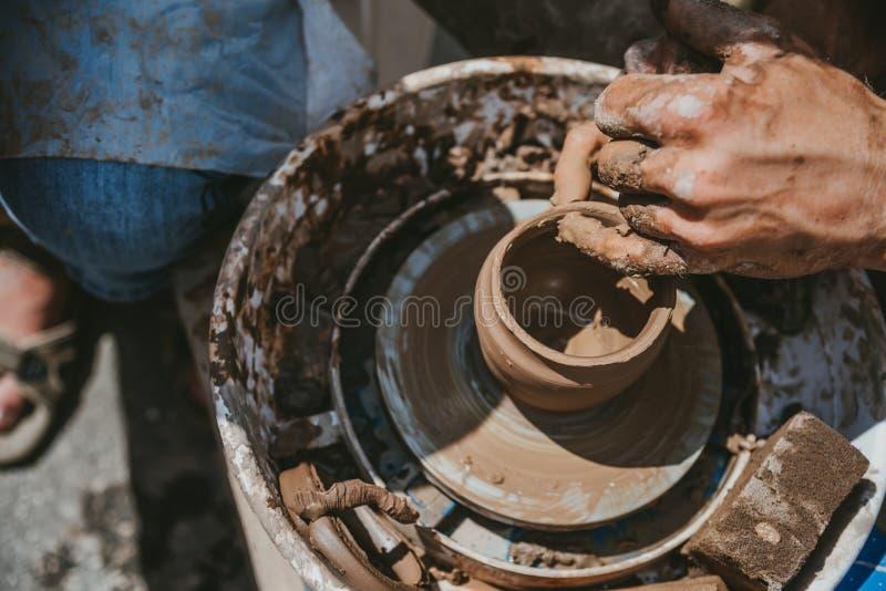 Ledar- händer gör en kruka av lera Mästarklass rymms i naturen, närbild royaltyfri fotografi