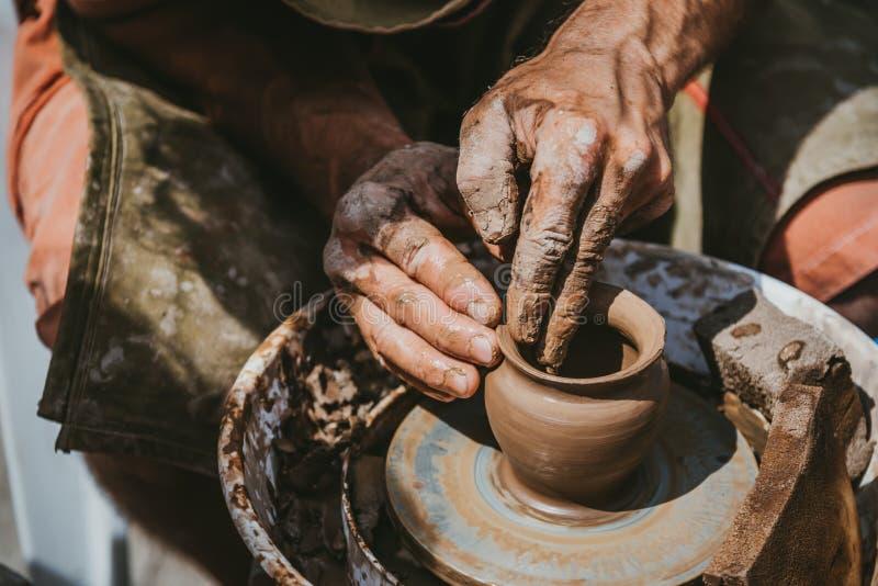 Ledar- händer gör en kruka av lera Mästarklass rymms i naturen, närbild arkivbilder