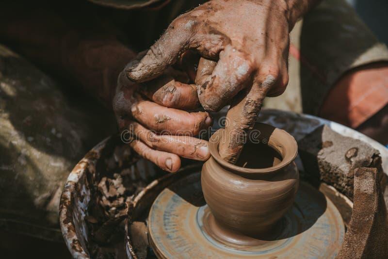 Ledar- händer gör en kruka av lera Mästarklass rymms i naturen, närbild royaltyfria foton