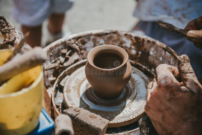 Ledar- händer gör en kruka av lera Mästarklass rymms i naturen, närbild arkivbild