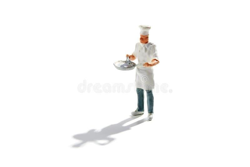 Ledar- kock i toque och förkläde med en panna arkivfoton