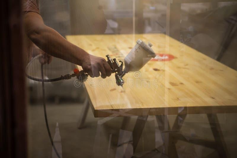 Ledar- målare i en fabrik - industriellt målningträ med sprutpistolen slapp fokus arkivfoton