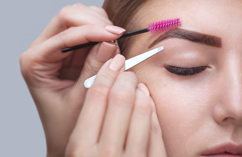 Ledar- makeup korrigerar och ger form för att dra ut med kirurgisk tång som målas föregående med hennaögonbryn royaltyfri bild
