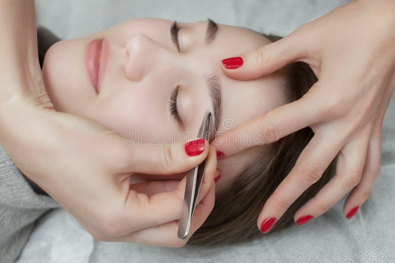 Ledar- makeup korrigerar och ger form för att dra ut med kirurgisk tång som målas föregående med hennaögonbryn i en skönhetsalong arkivbild
