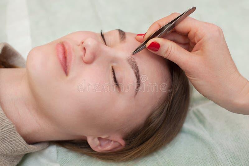Ledar- makeup korrigerar och ger form för att dra ut med kirurgisk tång som målas föregående med hennaögonbryn i en skönhetsalong royaltyfria bilder
