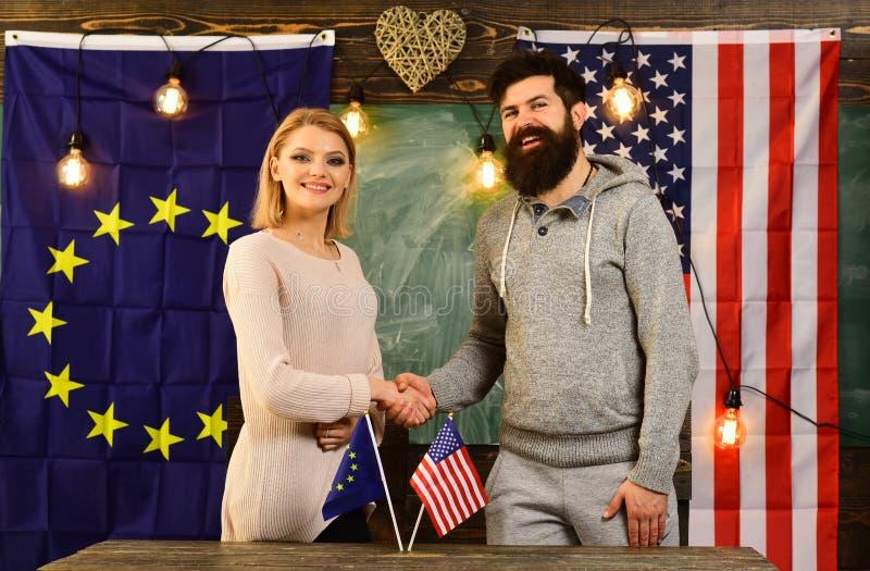 Ledare för europeisk union som och amerikanskakar händer på en avtalsöverenskommelse royaltyfri bild
