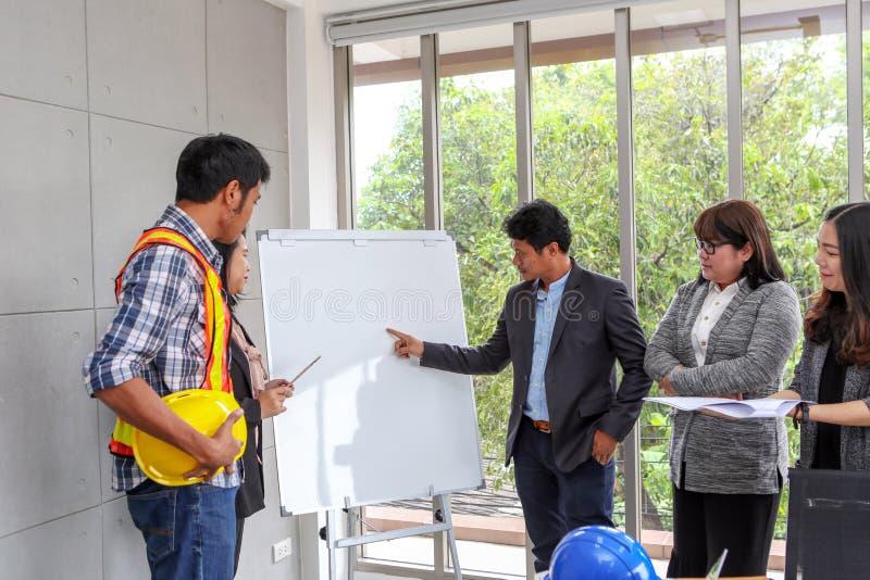 Ledare förklarar plan på en whiteboard säkert framstickande royaltyfria bilder