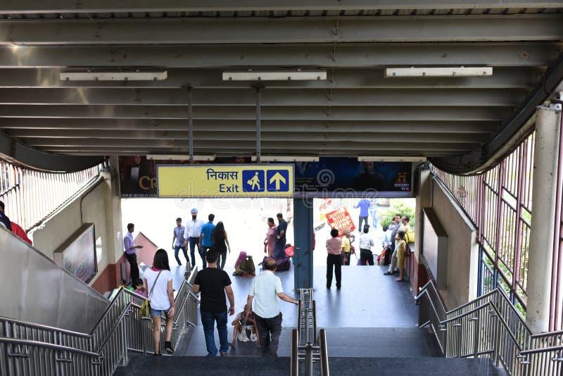 Ledare: Gurgaon Delhi, Indien: 06. Juni 2015: Folk som flyttar sig ut ur tunnelbanadrevet på den MG vägGurgaon stationen arkivbild