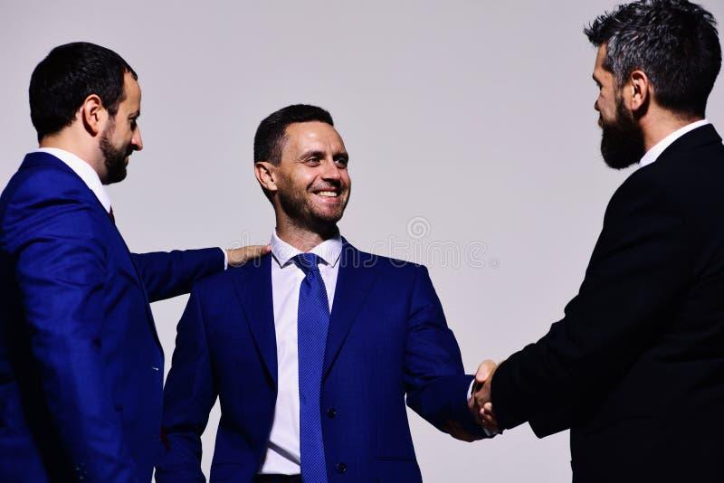 Ledare har avtal för danande för affärsmöte Affärsmän med lyckliga framsidor royaltyfria foton