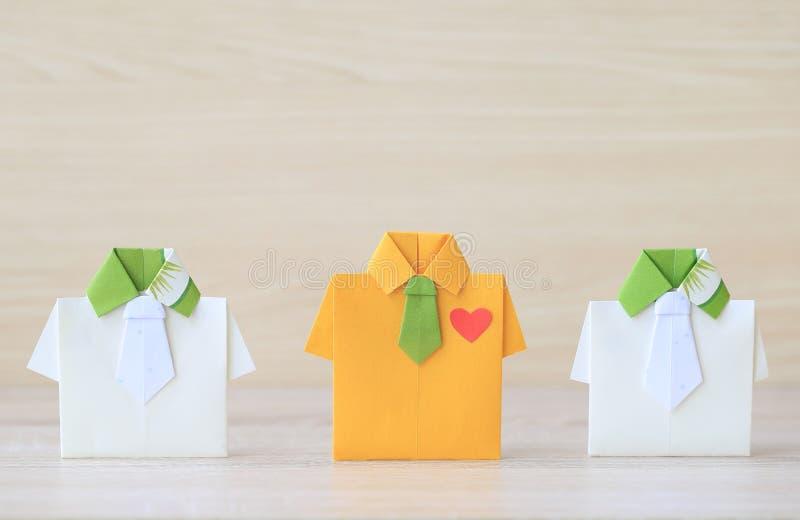 Ledarskap och teamworkbegrepp, gul skjorta för origami med bandet och leda bland den lilla gula skjortan på wooderbakgrund royaltyfri fotografi