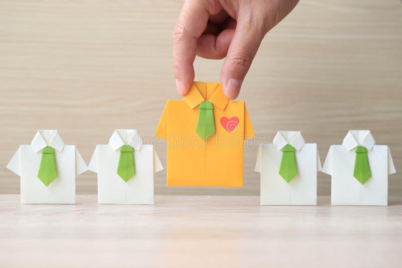 Ledarskap och teamworkbegrepp, kvinnahand som rymmer den gula skjortan för origami med bandet och leder bland den lilla gula skjo arkivfoto