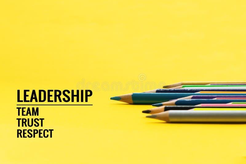 Ledarskapaffärsidé Blå färgblyertspennaledning annan färg med det ordledarskap, laget, förtroende och respekt på gul bakgrund arkivbild