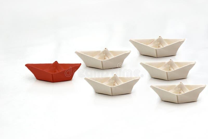 Ledarskapbegrepp med det röda pappers- skeppet som leder bland vit Pappers- vitt skeppbad bak det rött royaltyfria bilder