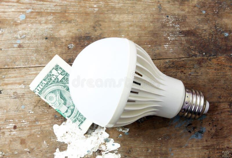 Ledd lampa med pengar arkivfoto