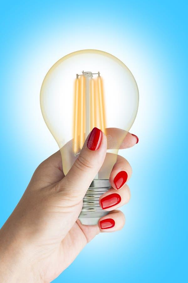 LEDD ljus kula för glödtråd i kvinnlig hand royaltyfria bilder