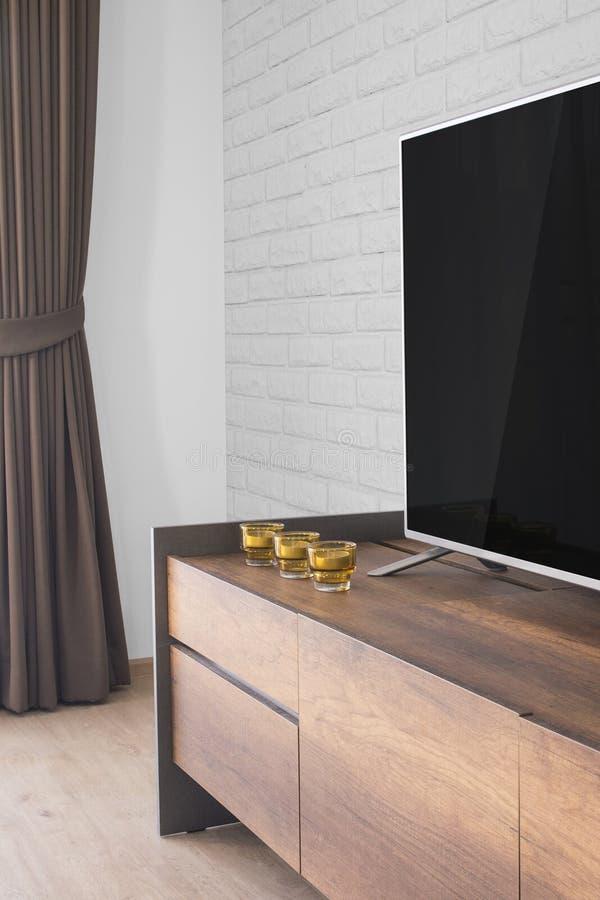 Ledd TV på TVställning med stearinljus och gardinen, vit tegelstenvägg royaltyfria bilder
