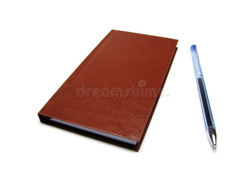 Leder ähnliche braune kleine Tagesordnung und blauer Kugelschreiber ohne Kappe stockbild